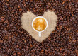 Heart from coffee beans and coffee cup in the center
