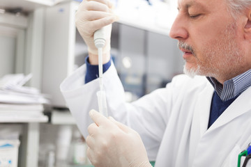 Close-up portrait of a male researcher filling a test tube