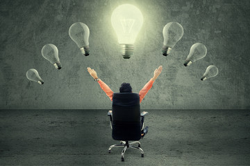 Successful businessman under lightbulb