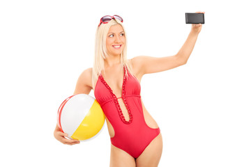 Sexy woman in a swimsuit taking a selfie