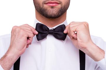 Man adjusting bow tie.