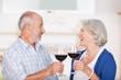 älteres paar stößt mit einem glas wein an