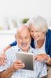 lachendes älteres paar schaut auf tablet-pc