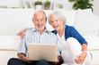 lachendes älteres ehepaar schaut auf laptop