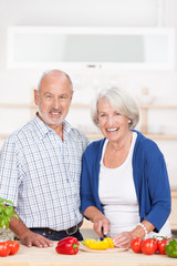 älteres ehepaar schneidet gemüse in der küche