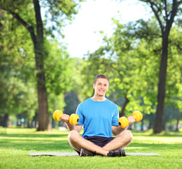 Man exercising with dumbbells in park