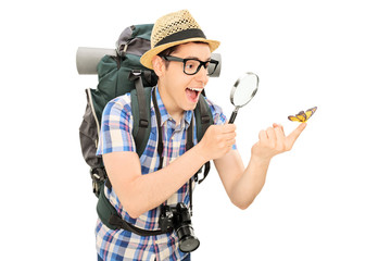 Hiker looking at a butterfly through a magnifier