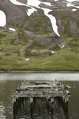 Iceland. Siglufjordur. Landscape with abandoned dock and mountai