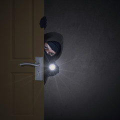 Thief sneaking through door
