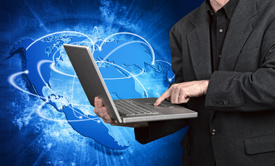 Blue vivid image of globe and man on laptop