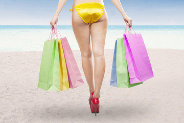 Woman holding shopping bags at beach