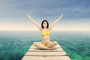 Woman in bikini meditating at shore