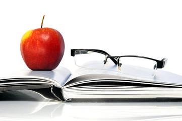 Offenes Buch mit Apfel und Nerd Brille