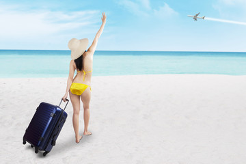 Woman in bikini with suitcase at beach