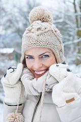 Lachende Frau mit Bommelmütze im Winter