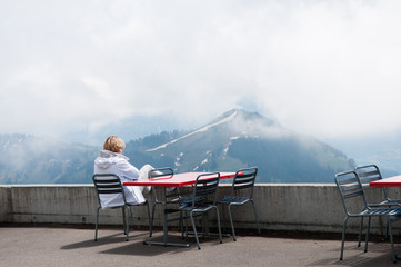 Woman sitting on the end of a mountain, overlooking the Alps