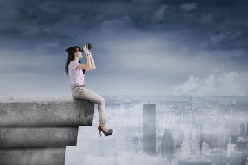 Young woman using binoculars on rooftop