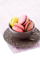Colorful macaroons in brown cup on white background