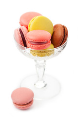 Colorful macaroons in glass vase on white background