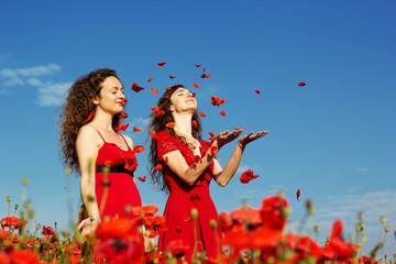 Two young women playing in poppies field