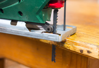 Close up  electric jigsaw cutting a pice of wood