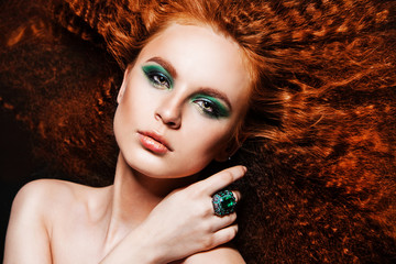 Red Hair. Fashion girl portrait with windy hair and ring
