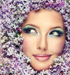 Funny beautiful model in flowers lilac sly looks in the side.