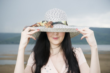 Portrait of a beautiful young woman in hat in summer