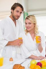 Cute couple in bathrobes smiling at camera together having break