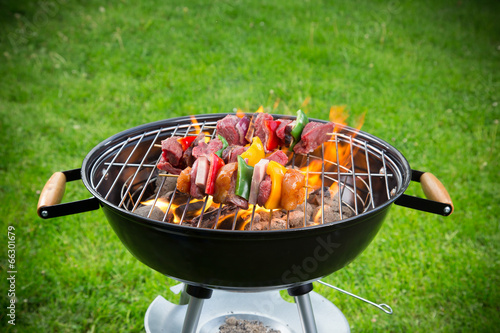 Fotobehang Vlees Tasty skewers on garden grill, close-up.