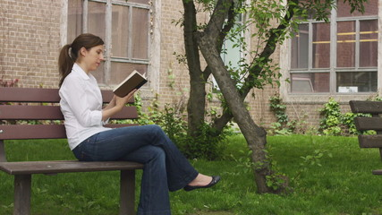 caucasian woman on a bench in a park reading a book