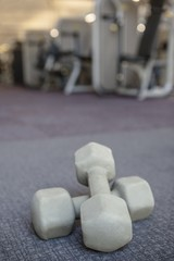 Grey dumbbells on the weights room floor