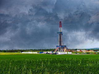 Natural gas drilling worksite with dramatic sky.