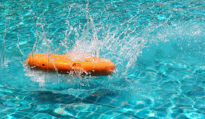 Orange life buoy is splashing with clear blue water in swimming