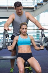 Personal trainer coaching female bodybuilder using weight machin