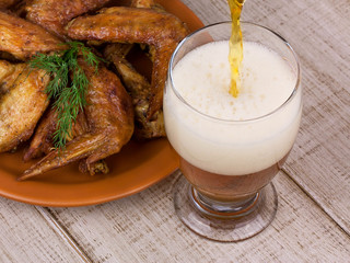 Beer and chicken wings on wooden background
