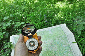 Compass in hand, against background of the map.