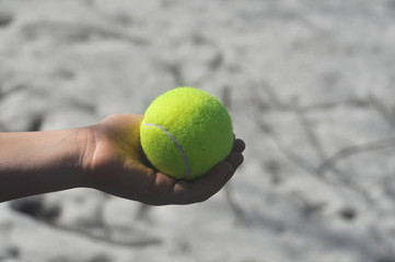 Tennis ball in his hand.