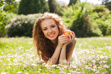 happy smiling young woman with apple laying on green grass