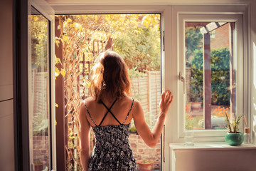 Woman standing in doorway at sunrise