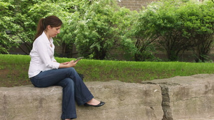caucasian woman in a park with tablet