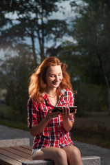 Ginger haired women  on park bench and tablet-pc