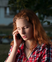 Ginger haired women on cell phone outdoors