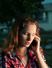 Redhead girl calling by mobile phone