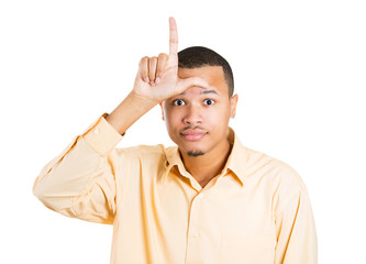 Portrait young man giving loser sign isolated white background