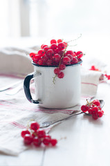 red currants in a white enamel mug
