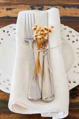 White plate serviette fork knife dried flowers