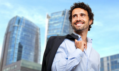 Smiling businessman holding his jacket outdoor