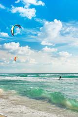 Kitesurfing. Kitesurfers rides the waves against sky.