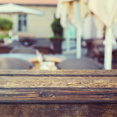 Wooden table over outdoor restaurant blur background